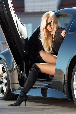 Glamorous blond babe sitting in tuned supercar photo
