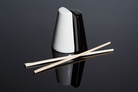 pepperbox: Salt-cellar and pepper-box and chopsticks on mirror surface Stock Photo