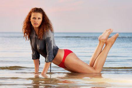 woman kneeling: Sexy woman kneeling in water on sunset