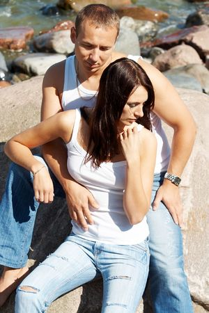 Young couple in blue jeans on a coast photo