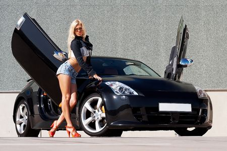 Sexy babe standing in front of tuned supercar