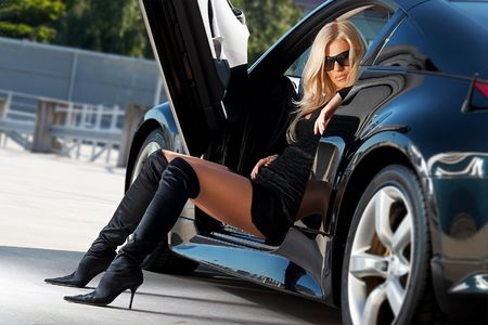 nude blond girl: Glamorous blond babe sitting in tuned supercar
