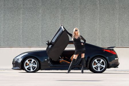 Glamorous blond babe standing near tuned supercar photo