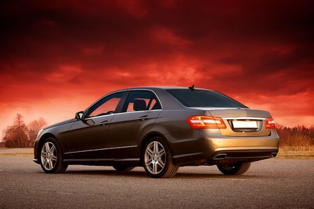 Modern luxury sedan with dramatic sunset sky Stock Photo - 5656470