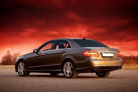 Modern luxury sedan with dramatic sunset sky
