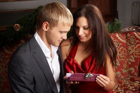 Young man presenting expensive gift to his girlfriend photo