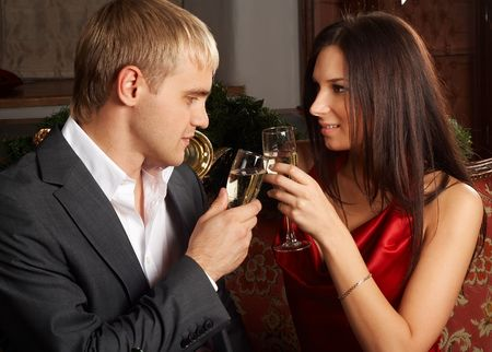 Young happy couple with champagne glasses at celebration photo