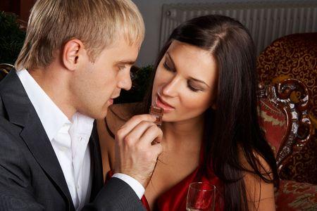 cioccolato natale: Giovane coppia felice mangiare cioccolato alla celebrazione