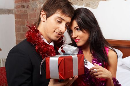 Romantic couple exchanging gifts on celebration photo