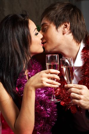 Young couple with champagne glasses kissing  photo