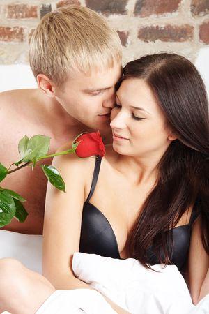parejas sensuales: Joven pareja en la cama con una rosa