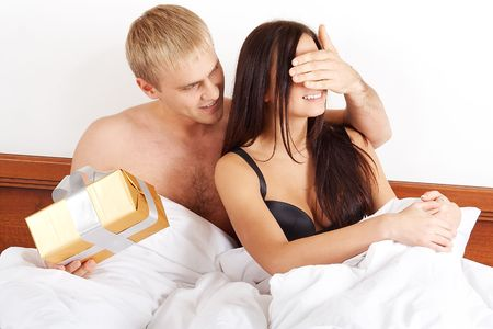 Young happy couple presenting gift in bed Stock Photo - 5829552