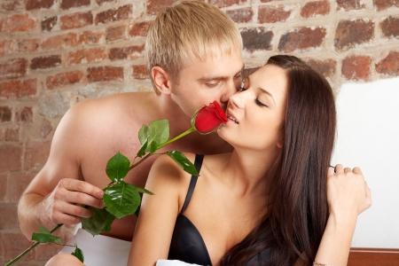 sexo cama: Joven pareja en la cama con una rosa  Foto de archivo
