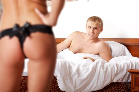Young woman teasing a man in bed Stock Photo - 5829547
