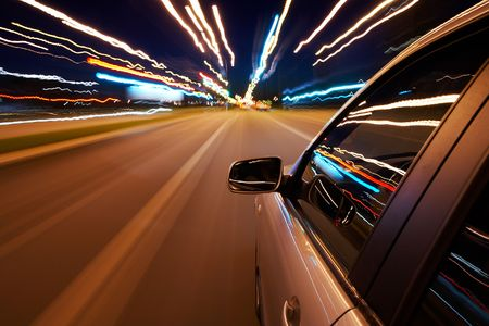 speeding car: Car driving fast on a night city road Stock Photo