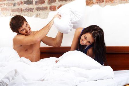 couple au lit: Jeune couple heureux ayant un oreiller combattre dans un lit