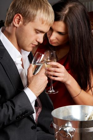 Glamorous young couple drinking champagne photo