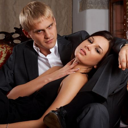 Young glamorous passionate couple sitting on a sofa photo