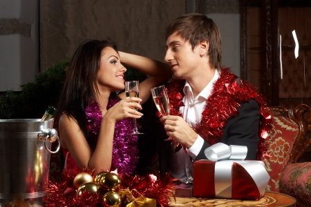 Young couple with champange glasses celebrating christmas photo