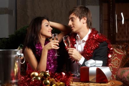 Young couple with champange glasses celebrating christmas photo