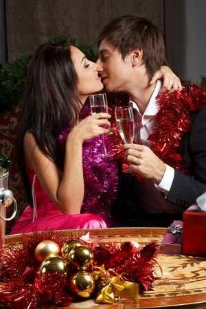 young couple kissing: Young couple with champange glasses kissing