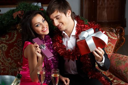 Young couple exchanging gifts on a New Year celebration photo