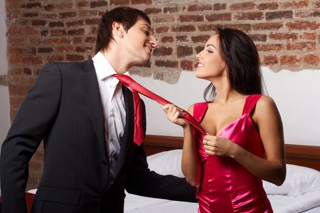 Young glamorous woman pulling a man by the red tie Stock Photo - 6181118