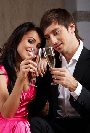 Glamorous young couple sitting on a sofa drinking champagne photo