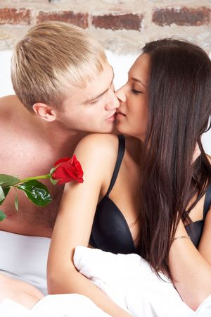 Young couple in bed with a rose  photo