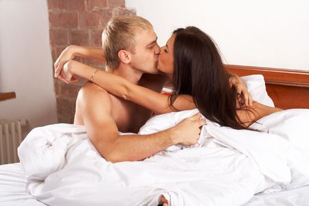 Young couple kissing in a bed photo