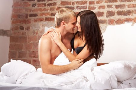 nude woman sex: Young couple having fun and laughing in bed