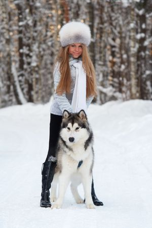 Young woman in winter park with dog photo