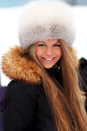 Young woman in fur-cap on a winter sea coast photo