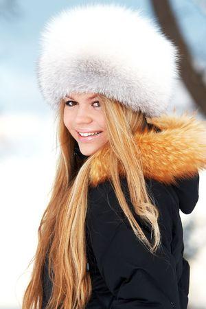 Young woman in fur-cap on winter sea coast photo