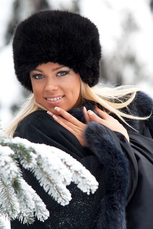 Beautiful blond lady in fur coat and hat in winter forest photo