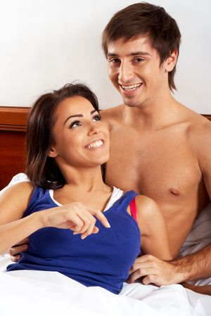 Young couple having fun and laughing in bed photo
