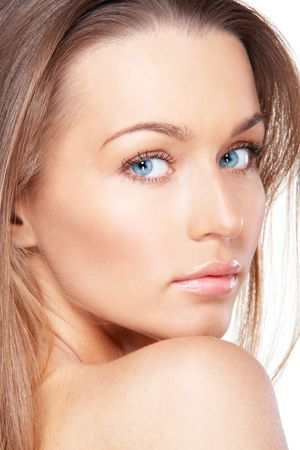 Closeup portrait of beautiful female model with blue eyes looking over a shoulder on white photo