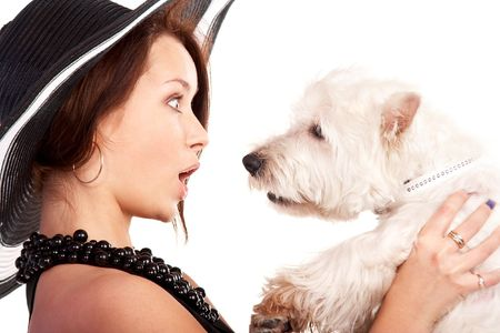 Young woman in a hat looking amazed at her little dog photo