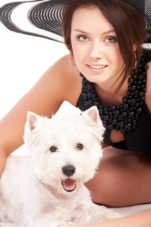 Young woman in a hat is happy to be with her little dog photo