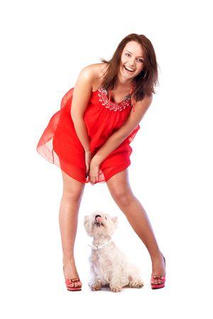 adentro y afuera: Mujer joven en vestido rojo y un poco perro colgando lengua aislado en blanco