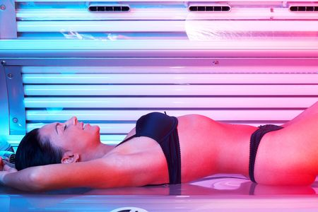 Beautiful young woman tanning in solarium Stock Photo
