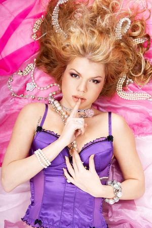 Young beautiful lady in a corset surrounded by jewelry on pink fabric showing gesture keep silence photo