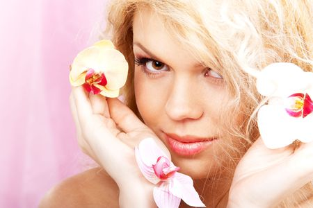 Closeup portrait of a beautiful young woman with orchids Stock Photo - 6607220