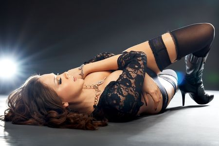 Glamorous young lying woman in black lingerie on black background