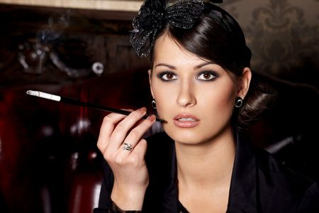 Glamorous brunette woman holding cigarette in mouthpiece in bar Stock Photo - 6917486