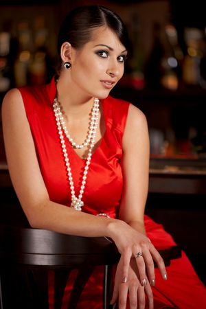 Glamorous brunette woman in pearl beads in bar Stock Photo - 6917481