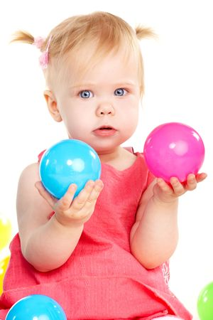 Little baby girl playing with two balls isolated on white photo