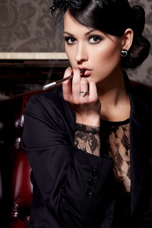 Glamorous brunette woman holding cigarette in mouthpiece in bar photo