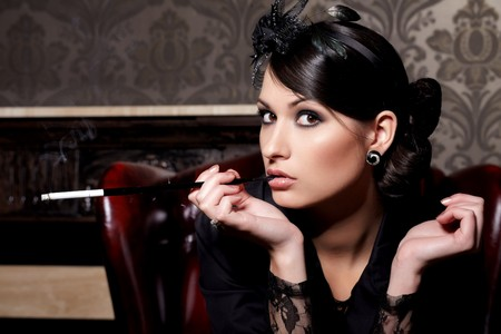 Glamorous brunette woman holding cigarette in mouthpiece in bar Stock Photo - 7013390