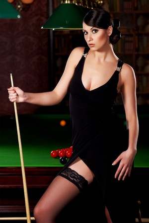 Glamorous brunette sexy woman with cue in snooker club photo